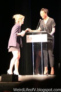 Emily Bett Rickards stops by the moderator\'s podium to talk to Aisha Tyler