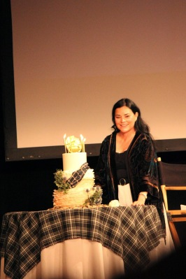 Diana posing with the birthday cake presented to her on stage at the Outlander Fan Even in Los Angeles.