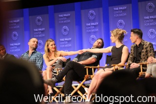 Katie Cassidy and Emily Bett Rickards hold hands over Stephen Amell