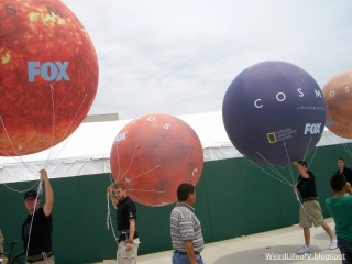 People walking around with large balloon planets promoting Cosmos - Outside San Diego Comic Con 2013.