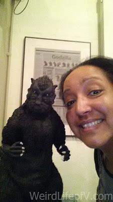 Posing with a Godzilla statuette