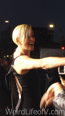 Charlize Theron smiling at fans in the fan pit.