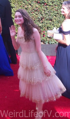 Emily Robinson waving to fans on the 2016 Emmys red carpet