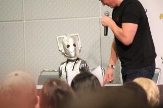 John Barrowman invites a little girl dressed as a Cyberman on stage