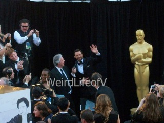 Hugh Jackman waving to the fans while being interviewed by Chris Connelly at the 2013 Academy Awards