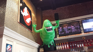 Slimer in the corner and Ghostbusters playing on the tvs.