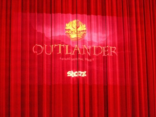Outlander projected onto the red curtain inside the Orpheum Theatre in Los Angeles