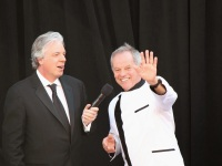 Chris Connelly interviewing Wolfgang Puck, who\'s waving to the fans, on the red carpet for the 2013 Oscars.